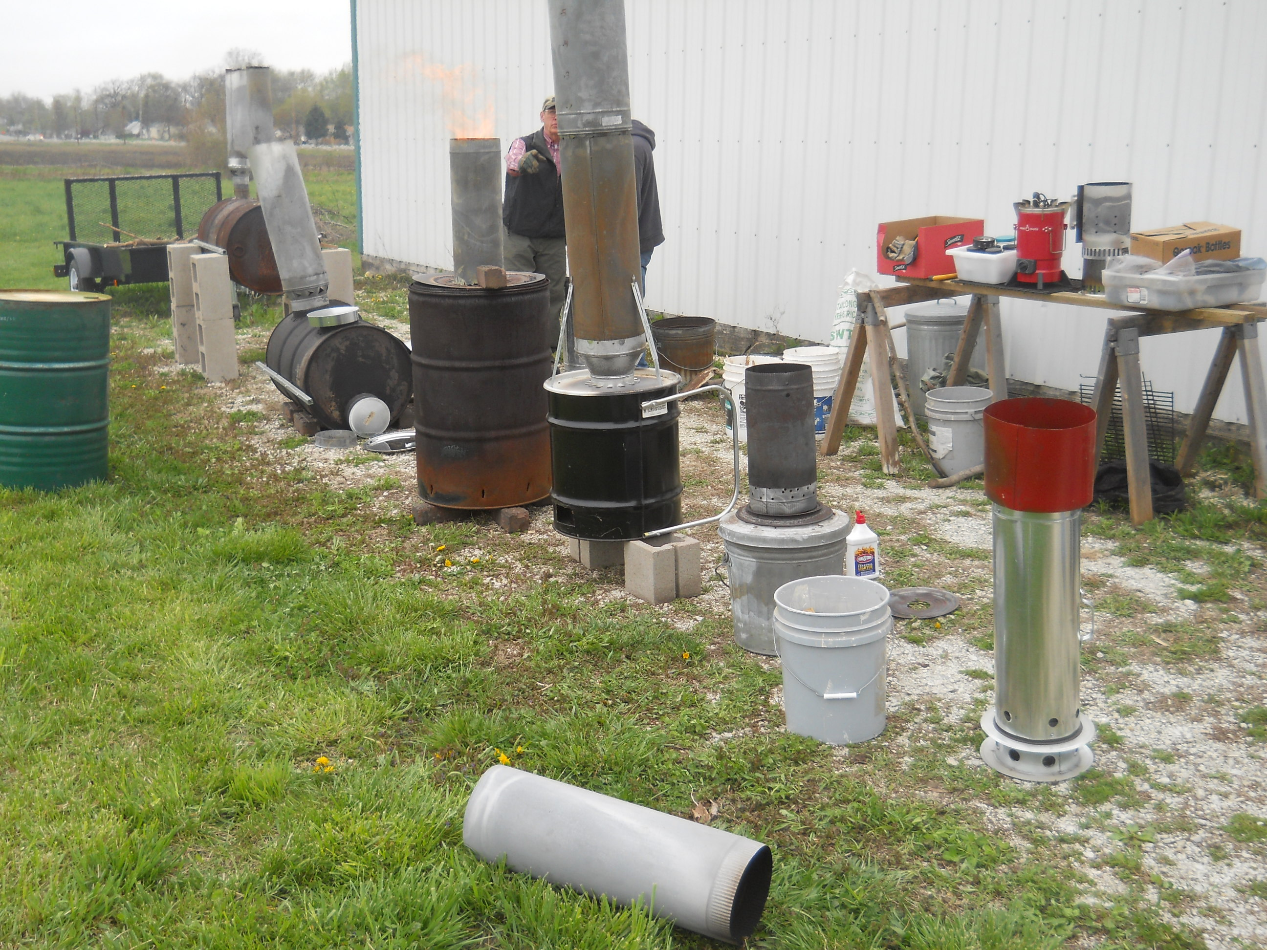 various sizes of cookstoves and char-makers lined up outside with several lit for demonstrations